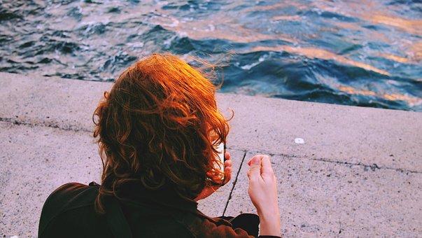 スマホを眺めて落ち込む女性