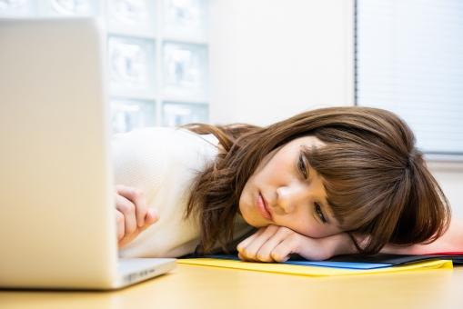 疲れた顔でパソコンを眺める