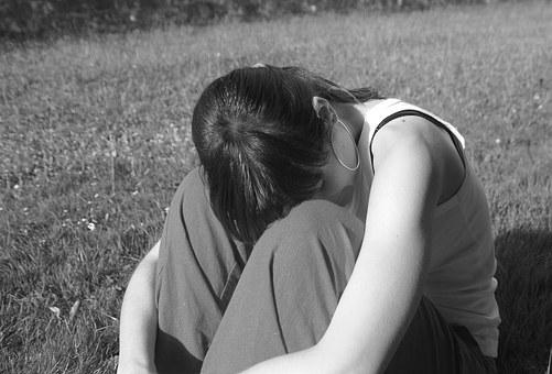 膝を抱える女性の写真