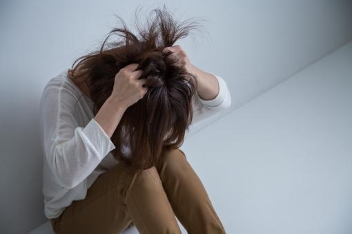 膝を抱え頭をかきむしる女性