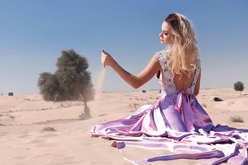 砂漠で座り込む女性
