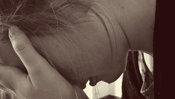 顔を覆って絶望する女性