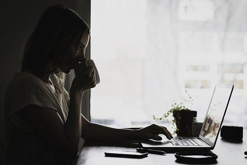 コーヒー片手にパソコンを操作する女性