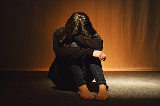 膝を抱えて絶望する女性