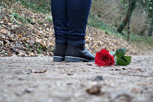 女性の足元に落ちているバラ