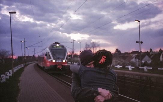 駅のホームで抱き合うカップル