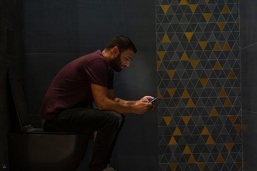 トイレでスマホを操作する男性