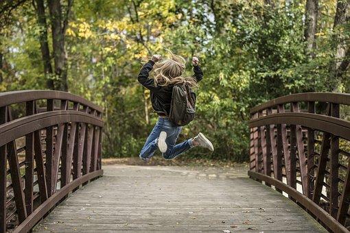 橋の上で喜んでジャンプする女性