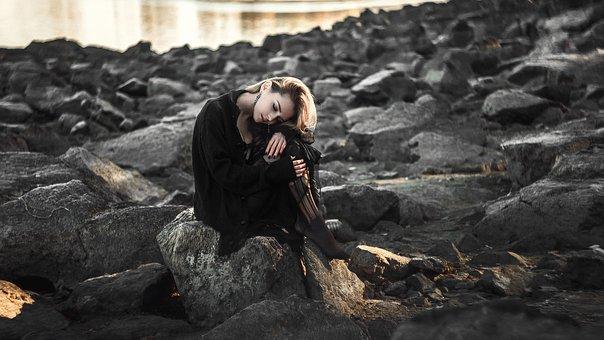 堤防に座っている悲しそうな女性