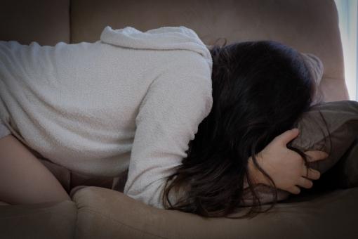 ソファーに顔を埋めて泣く女性