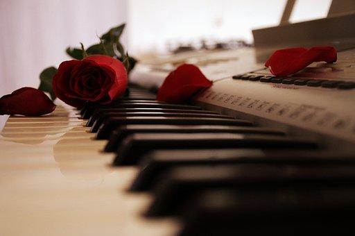 ピアノと鍵盤の上の赤いバラ