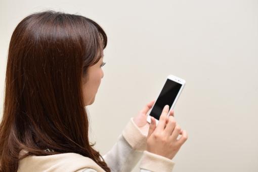 スマホを操作する女性の写真